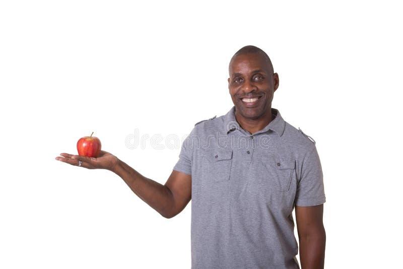 Man som rymmer ett äpple arkivbild