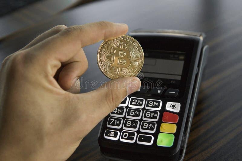 Man som rymmer ett Bitcoin mynt med en pos.-terminal på bakgrund Bitcoins cryptocurrency E-kommers affär, finans royaltyfri foto