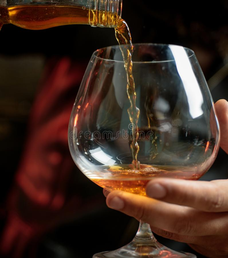 Man som rymmer ett exponeringsglas av whisky Läppja whisky Degustation avsmakning royaltyfria bilder