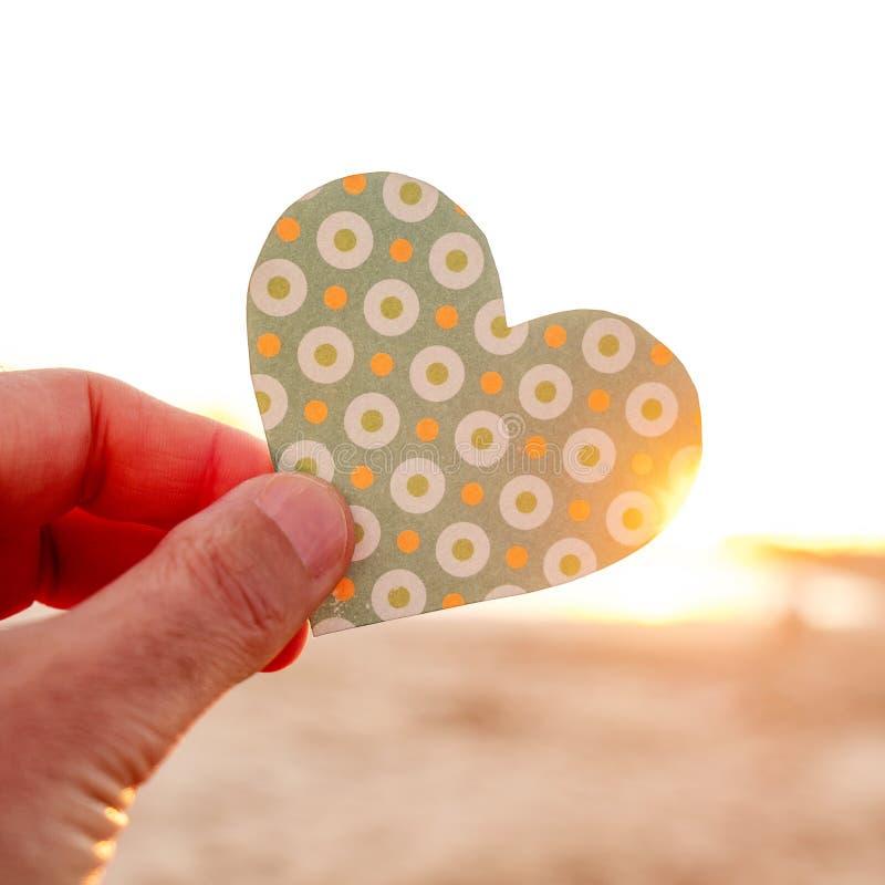 Man som rymmer ett hjärtasnitt på gryning eller solnedgången arkivbilder