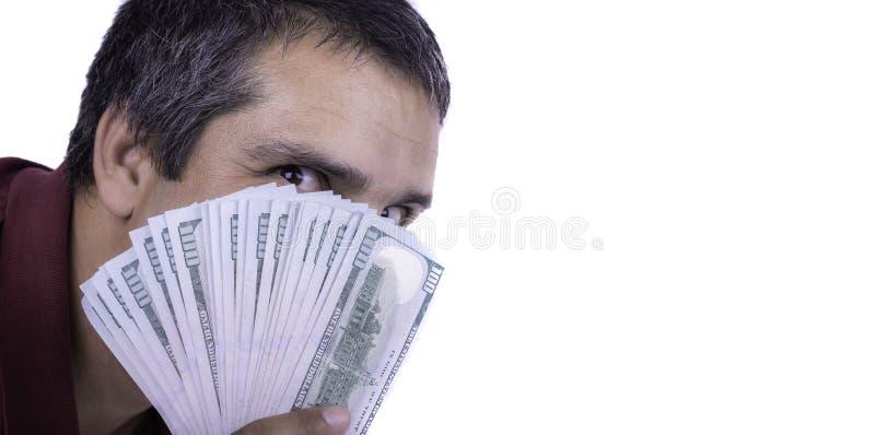 Man som rymmer ett utbrett av hundra dollarräkningar som täcker hans framsida som ser direkt på girigt tillfredsställt lustful fö royaltyfri bild