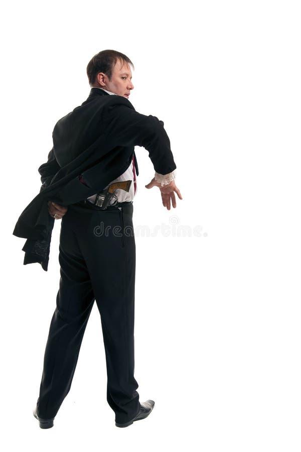 Man som rymmer ett vapen bak hans baksida royaltyfria foton
