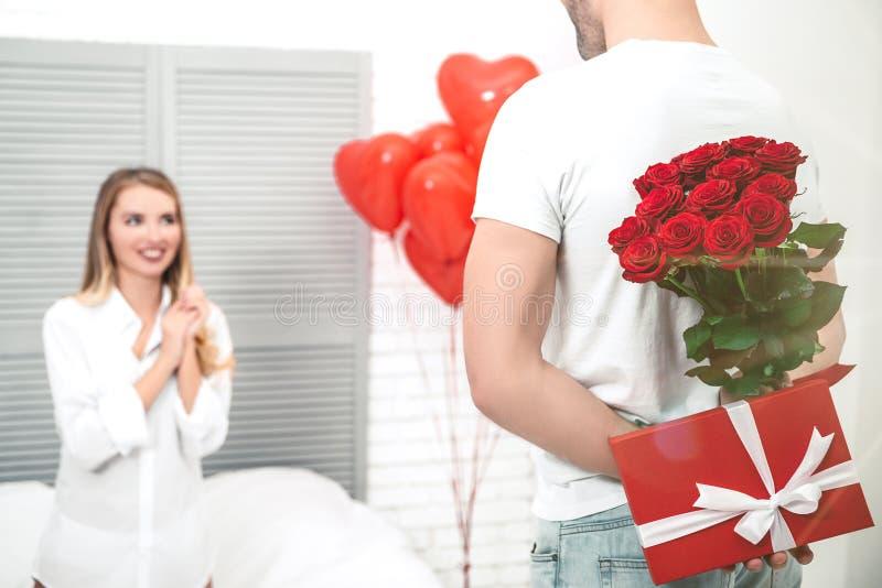 Man som rymmer gåvor för hans flickvän bak en baksida arkivbilder