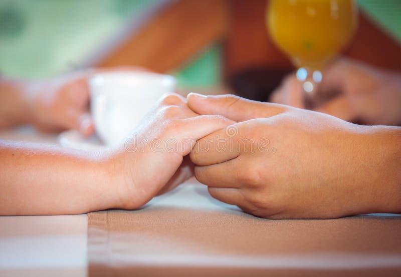 Man som rymmer hans flickväns hand på kafét fotografering för bildbyråer