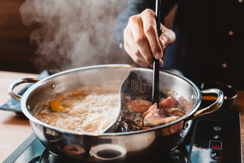 Man som rymmer medelsällsynt skivaWagyu A5 nötkött ut från varm grund för soppa för krukashabushoyu vid pinnar med ånga royaltyfria bilder