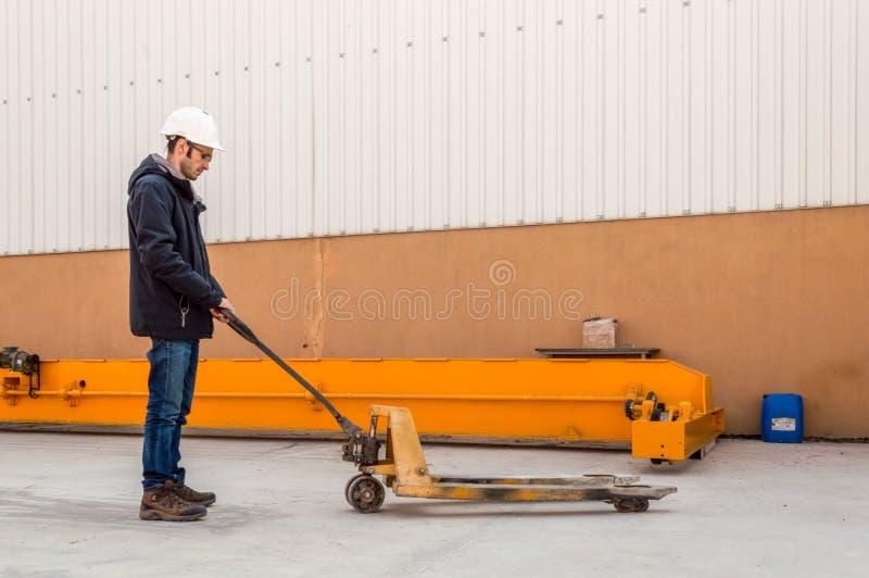 Man som rymmer tom manuell utrustning för lastbil för gaffeltruckpalettutmatningsfack i efterbehandlaren royaltyfria foton