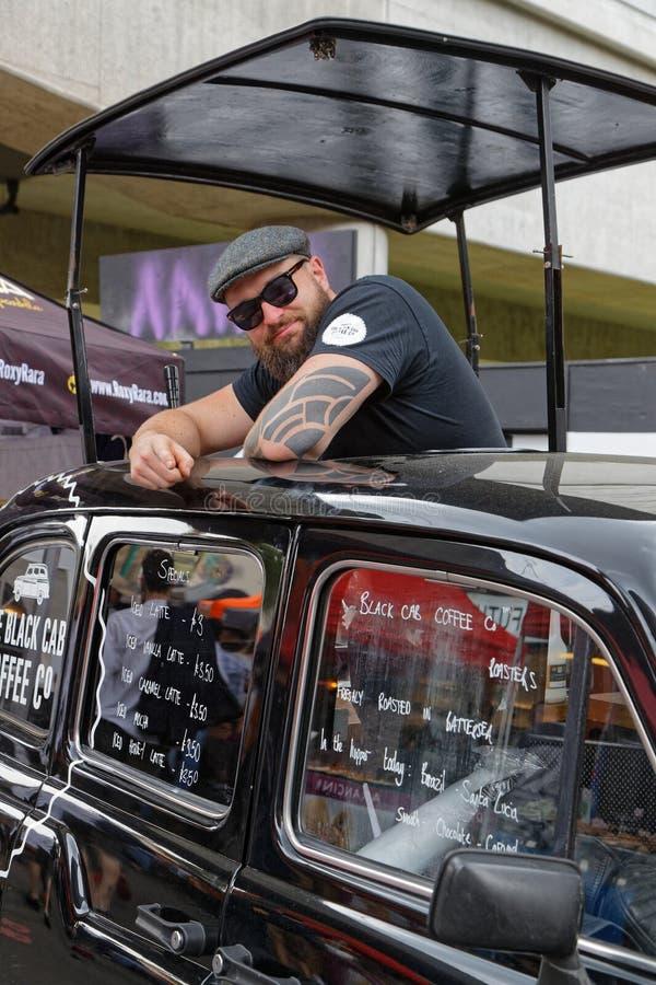 Man som säljer kaffe i en svart taxi på tegelstengrändmarknaden royaltyfria foton
