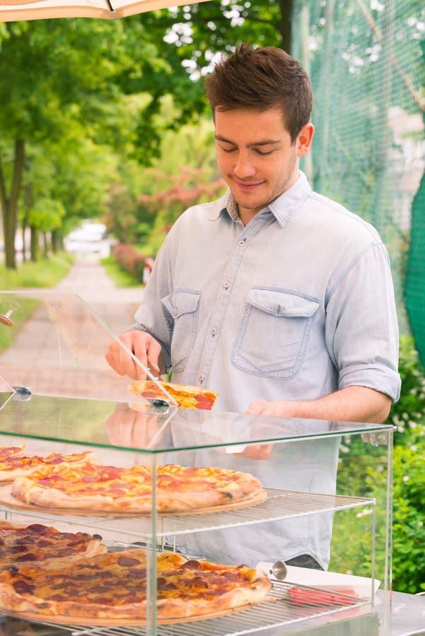 Man som säljer pizza vid skivan royaltyfri foto
