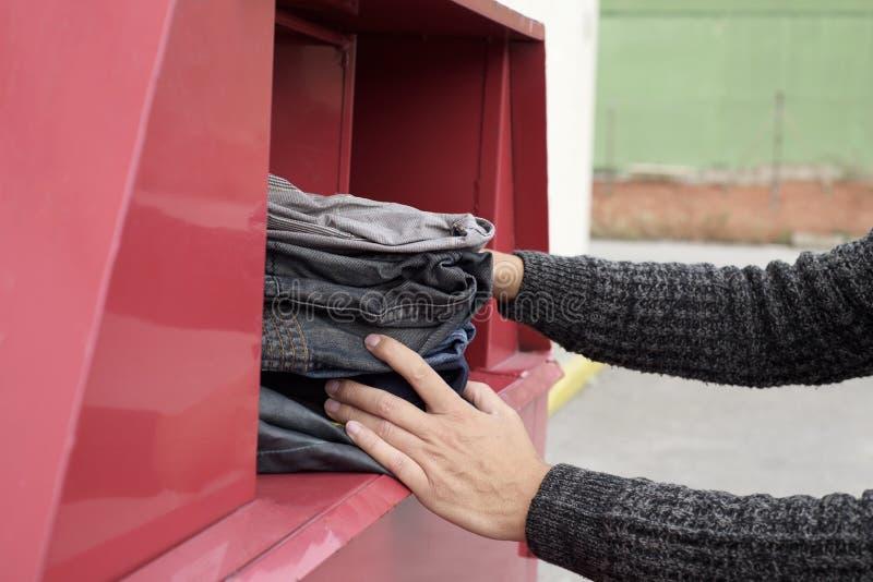 Man som sätter in använd kläder i ett klädfack arkivfoto