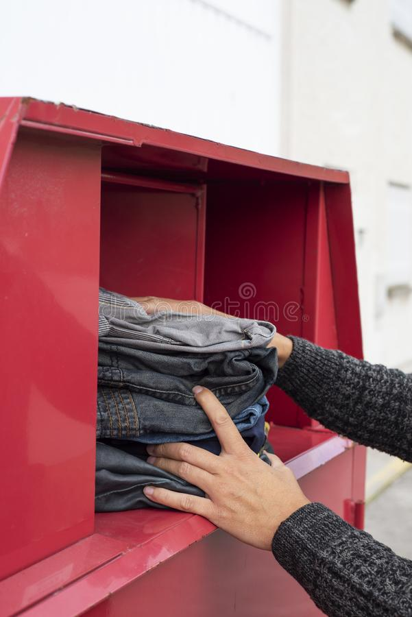Man som sätter in använd kläder i ett klädfack royaltyfri foto