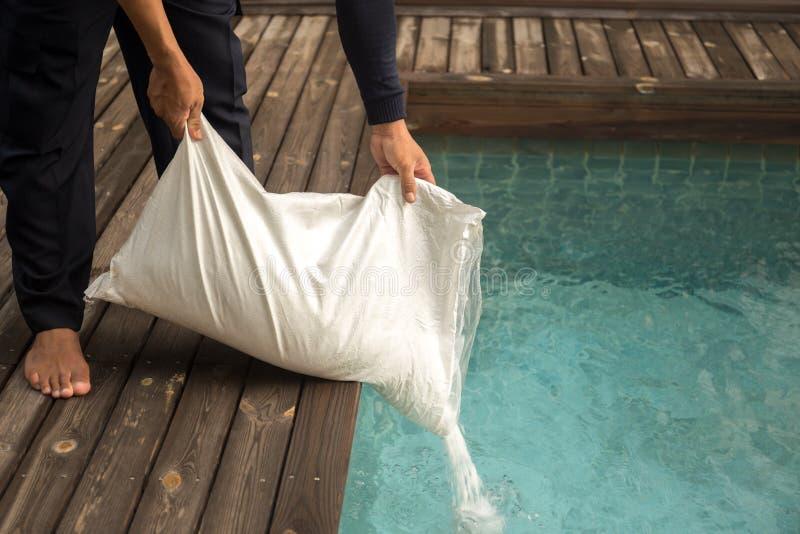 Man som sätter den salta chlorinatoren för behandlingvatten i simningbajs arkivbild