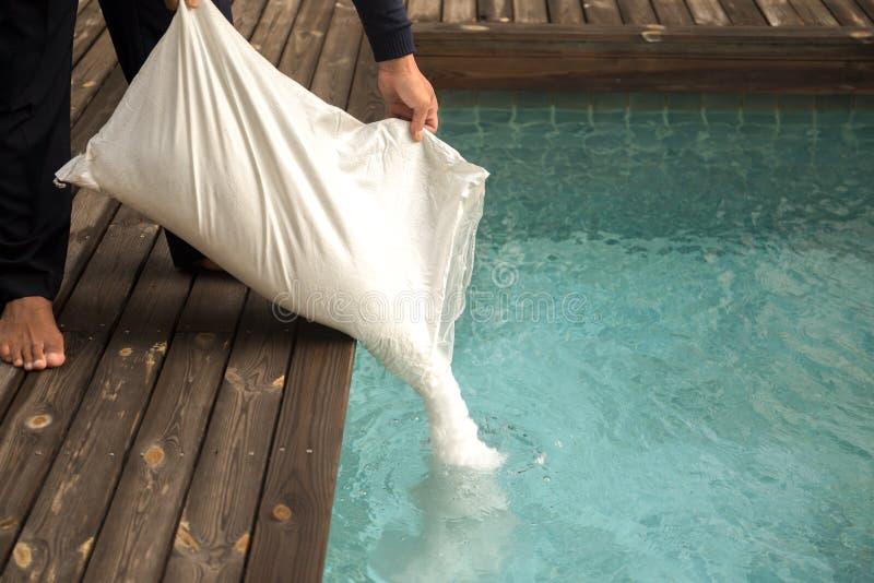Man som sätter den salta chlorinatoren för behandlingvatten i simningbajs royaltyfri fotografi