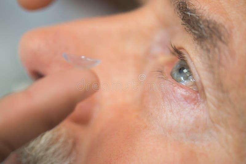 Man som sätter kontakten Lens i öga royaltyfri foto