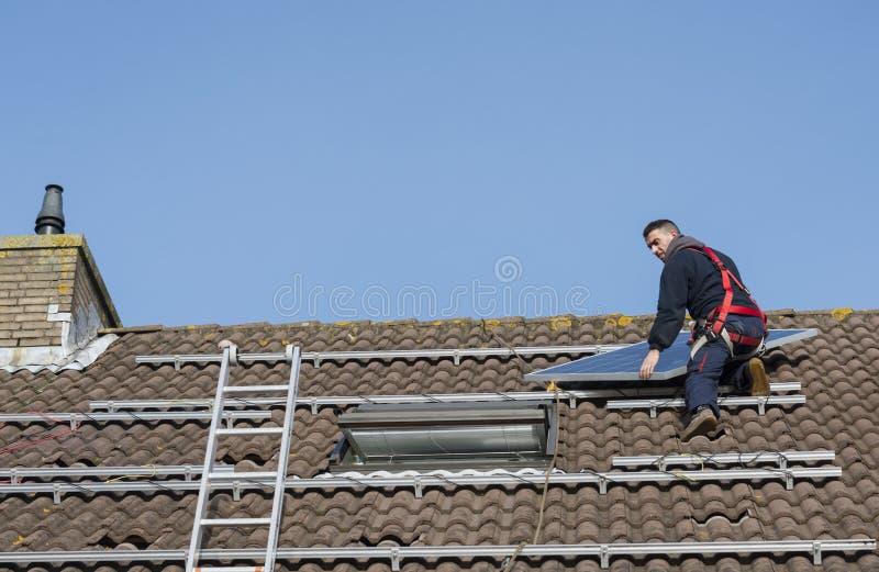 Man som sätter solpanelen på taket royaltyfri foto