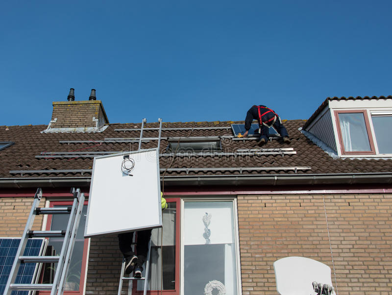 Man som sätter solpanelen på taket royaltyfri fotografi