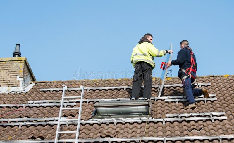 Man som sätter solpanelen på taket fotografering för bildbyråer