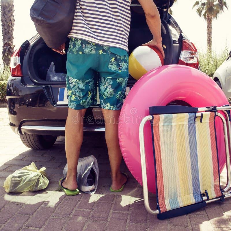 Man som sätter strandmaterial i bilen royaltyfri fotografi