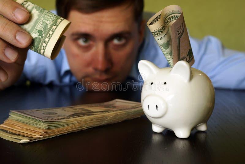 Man som sätter valuta i spargrisen royaltyfri fotografi