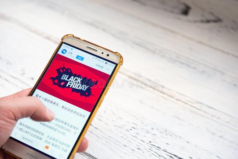 Man som söker efter nyheterna som talar om Black Friday försäljningar vid mobilen royaltyfri bild