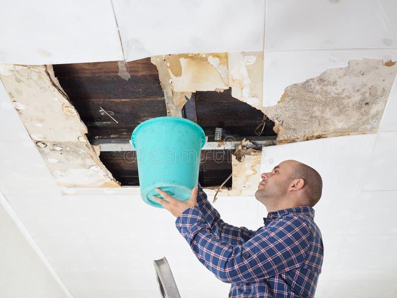 Man som samlar vatten i hink från tak arkivbilder