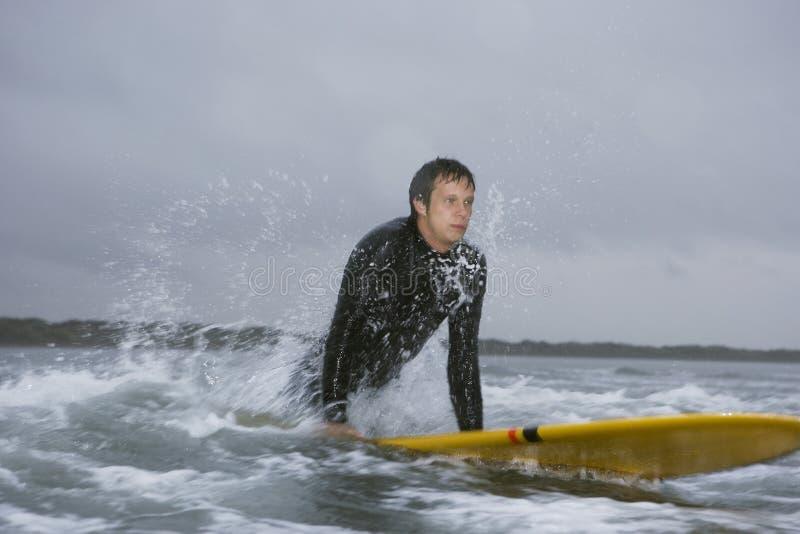 Man som ser bort, medan surfa i vatten på stranden arkivfoto