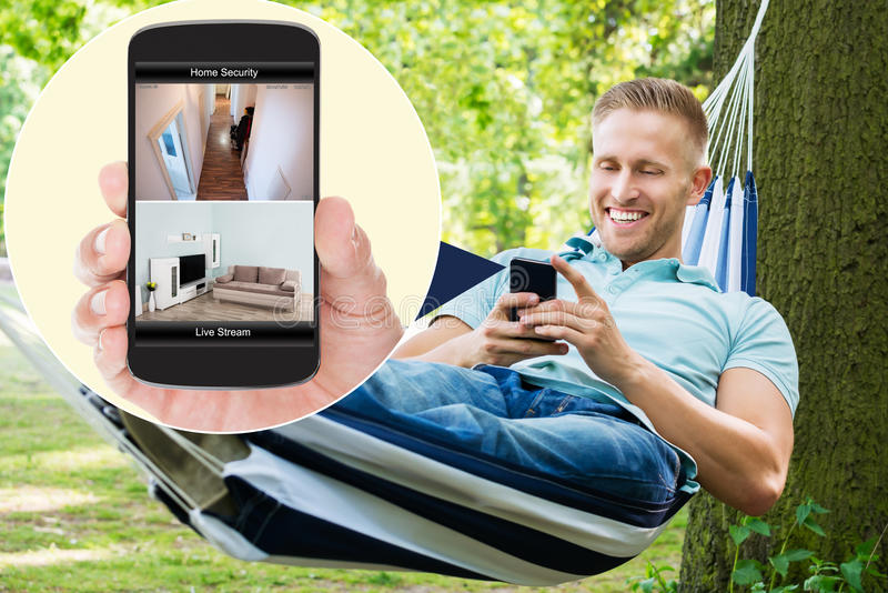 Man som ser det hemmastadda säkerhetssystemet på mobilephonen royaltyfria bilder