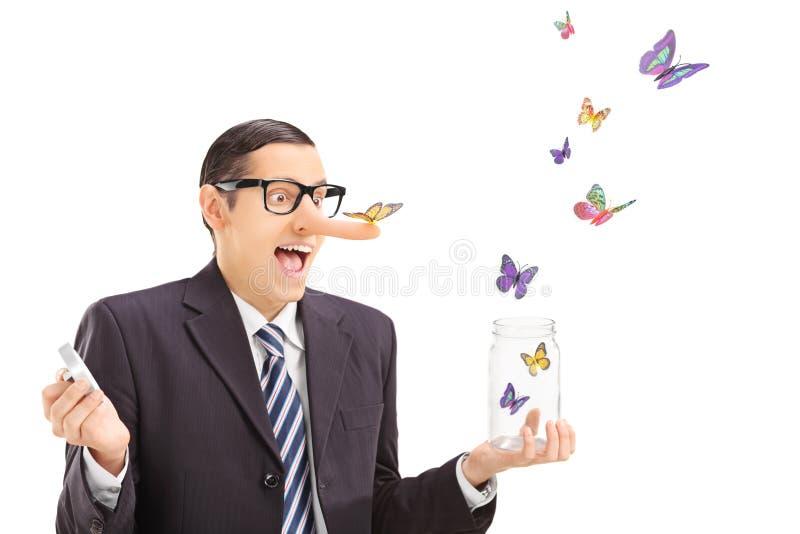 Man som ser fjärilar som flyr en öppen krus arkivbild