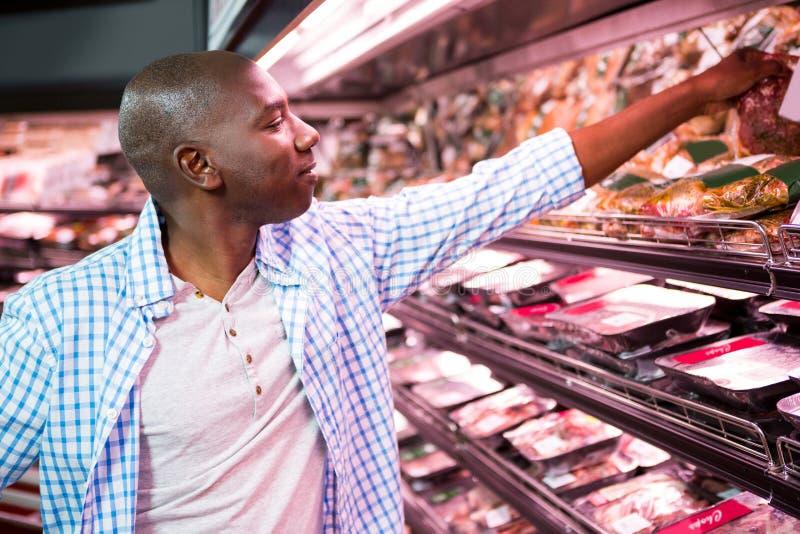 Man som ser gods i livsmedelsbutikavsnitt, medan shoppa arkivfoto