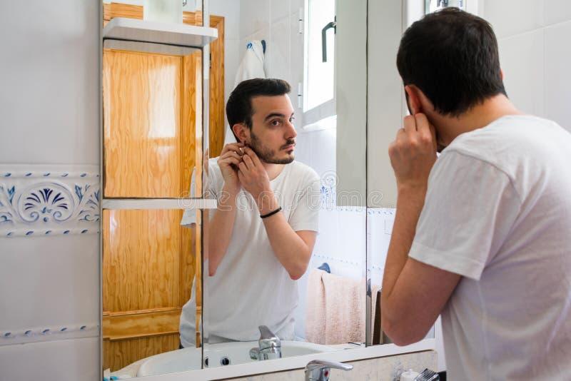 Man som ser honom i en spegel i badrummet Han får ett örhänge arkivfoton
