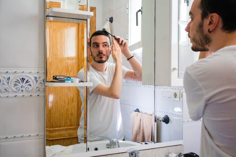 Man som ser honom i en spegel i badrummet Han kammar hans h?r arkivbild
