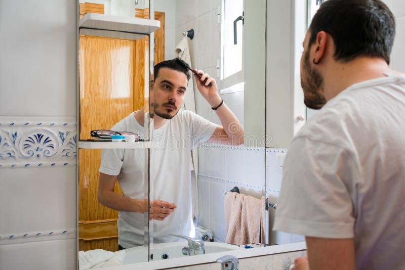 Man som ser honom i en spegel i badrummet Han kammar hans h?r royaltyfri bild