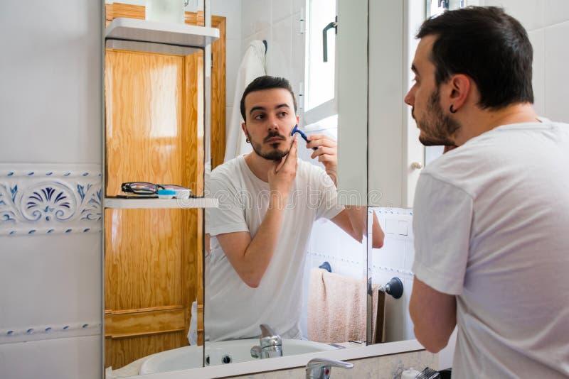 Man som ser honom i en spegel i badrummet Han rakar hans skägg royaltyfri foto