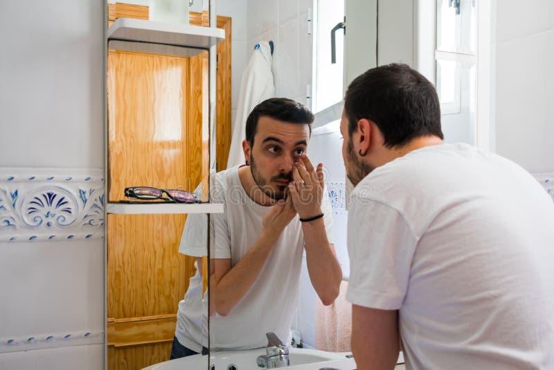 Man som ser honom i en spegel i badrummet Han sätter en lins royaltyfria foton