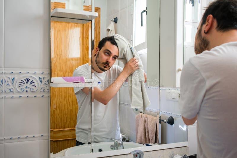 Man som ser honom i en spegel i badrummet Han torkar hans hår med en handduk fotografering för bildbyråer