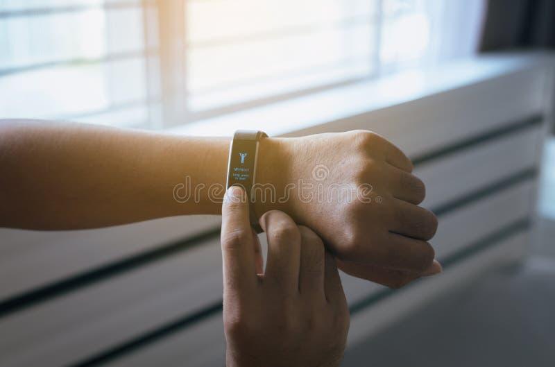 Man som ser med bildskärmen för hjärtahastighet och använder genomkörarefunktionsläge på smartwatch efter vak upp i morgonen arkivfoto