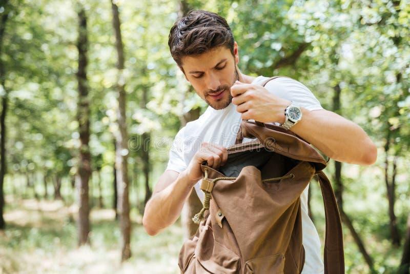 Man som ser något i ryggsäck på skogen royaltyfria foton