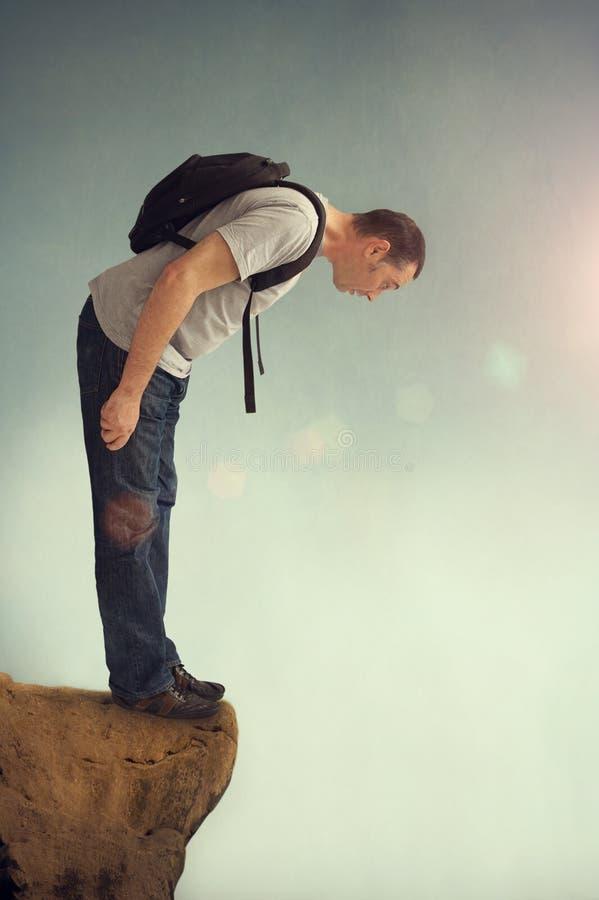 Man som ser ner från en stenig avsats arkivfoton