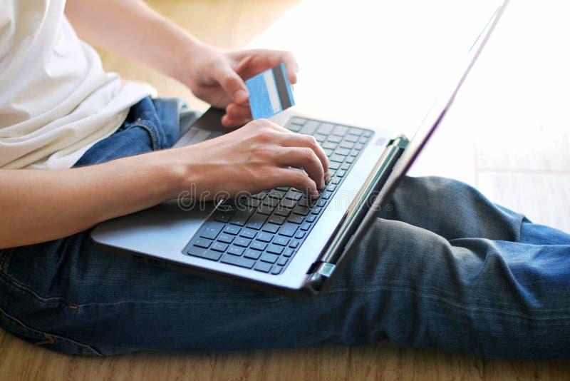Man som shoppar direktanslutet genom att använda bärbara datorn arkivbilder