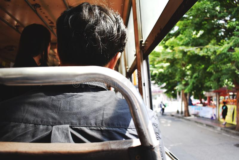 Man som sitter i bussen som rider för att arbeta royaltyfri bild