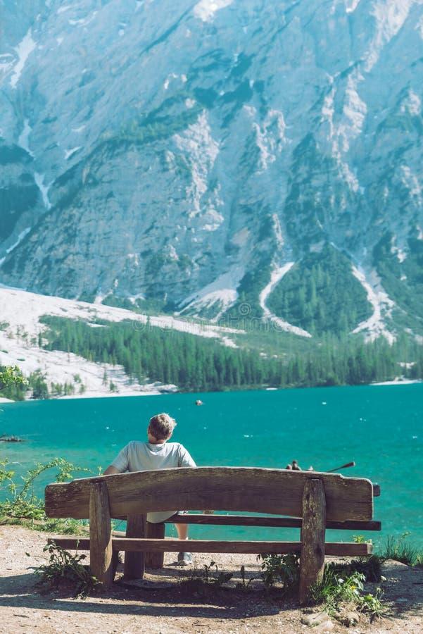 man som sitter på bänken som tycker om sikten av sjön i berg royaltyfri fotografi