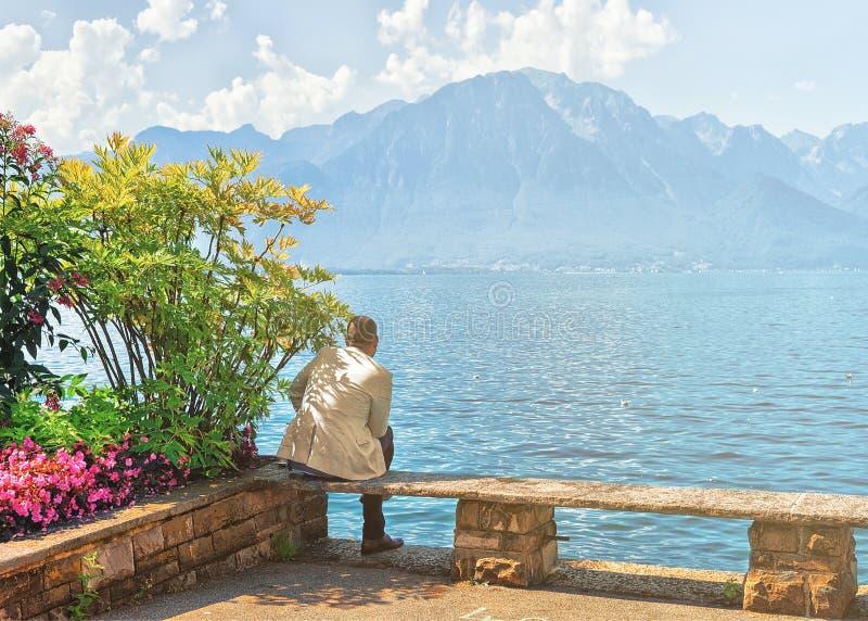 Man som sitter på bänkinvallning av Genève sjöMontreux sommar royaltyfri bild