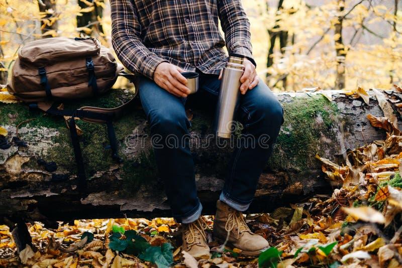 Man som sitter på den stupade trädstammen med termoset royaltyfri fotografi