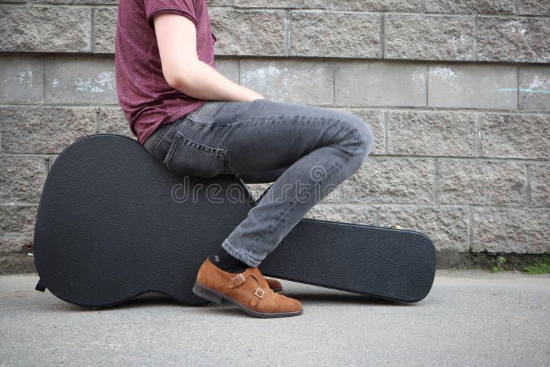 Man som sitter på ett svart gitarrfall H?rt fall f?r elektrisk gitarr arkivfoto