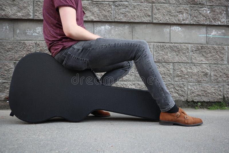Man som sitter på ett svart gitarrfall H?rt fall f?r elektrisk gitarr royaltyfria bilder