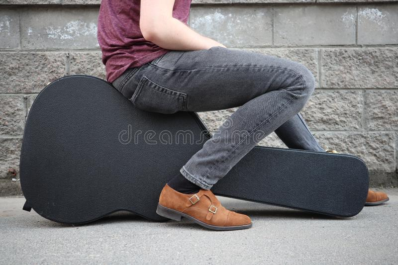 Man som sitter på ett svart gitarrfall H?rt fall f?r elektrisk gitarr arkivfoton