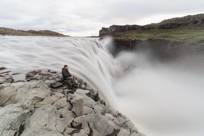Man som sitter på klippkanten bredvid den Dettifoss vattenfallet i den Vatnayokull nationalparken, Island royaltyfri fotografi