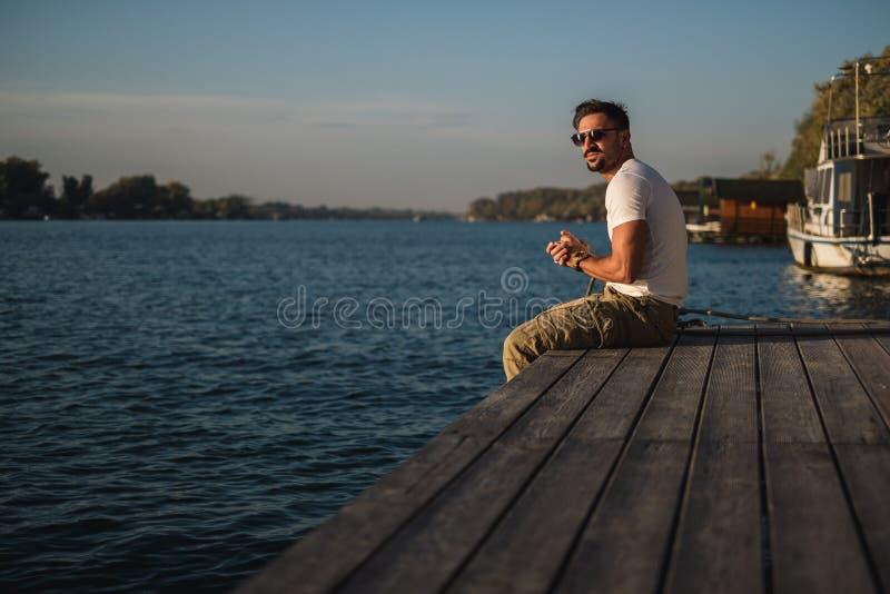 Man som sitter på pir och ser solen royaltyfri bild
