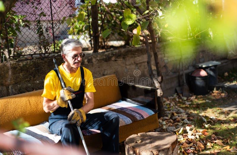 Man som sitter på soffan, når att ha gjort ren i gården arkivbild