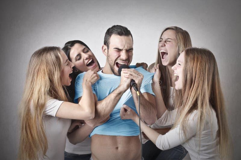 Man som sjunger med fyra kvinnor runt om honom fotografering för bildbyråer