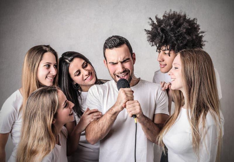 man som sjunger med hans vänner  royaltyfria bilder